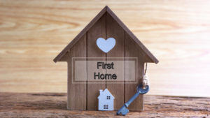 """Image of small wooden home with sign saying """"First Home"""""""